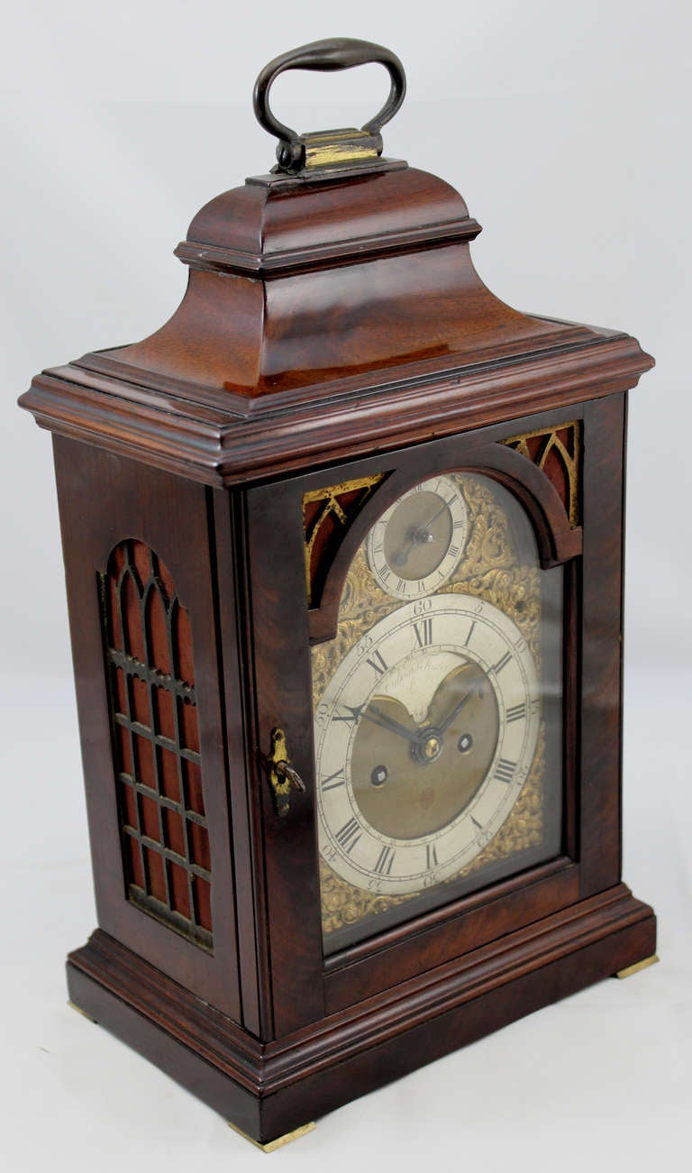 """This English mahogany table or bracket clock with bail handle is circa 1765, with a  composite brass dial with recessed 4 ½"""" maker's boss marked Edward Foster, London.. It has a Roman numeral chapter ring with calendar ring engraved 1-31 around the"""
