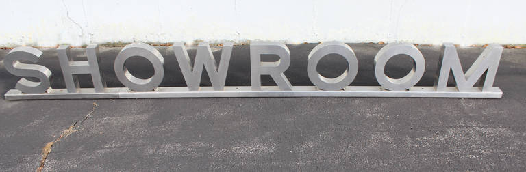 A great mid 20th century polished stainless steel Showroom advertising sign, probably from a auto dealership or large urban department store, hollow letters with open backs, each attached to a steel support base.