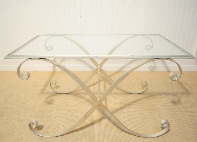 Vintage Italian Hollywood Regency style iron and glass coffee table. Item features a silver finish to the whimsical scrolling X-form frame, stretcher base, inset clear glass top and elegant Hollywood Regency form.