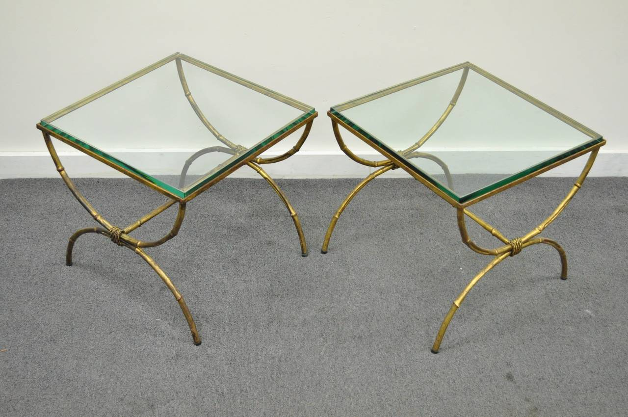 "Elegant pair of Italian made, Vintage Hollywood Regency, Gold Gilt Metal Faux Bamboo form Side or End Tables with substantial 5/8"" thick square glass tops. The pair features x-form curule stretcher bases, rope detailing, and very classy overall form."