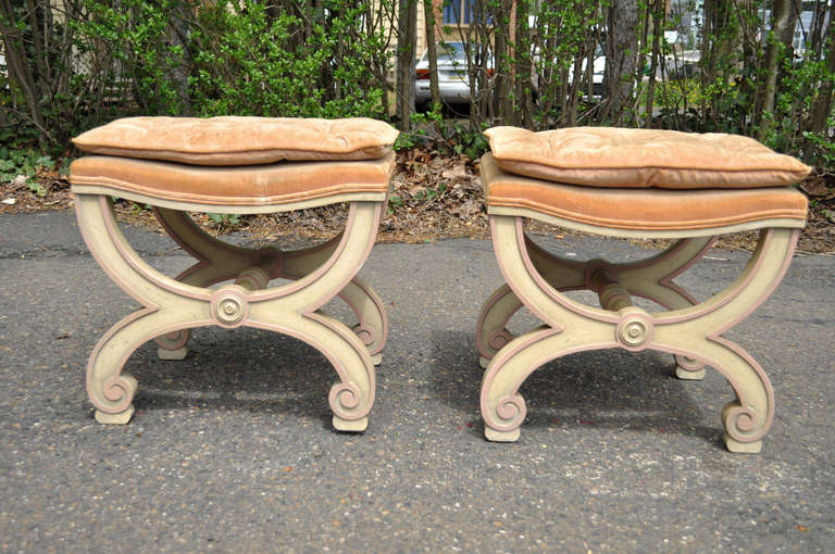Pair of vintage French Hollywood Regency / neoclassical style X-frame benches. The stools feature solid wood carved frames with scroll style X-form legs, and lightly distress painted cream and pink finish. Stools are in the Dorothy Draper style and