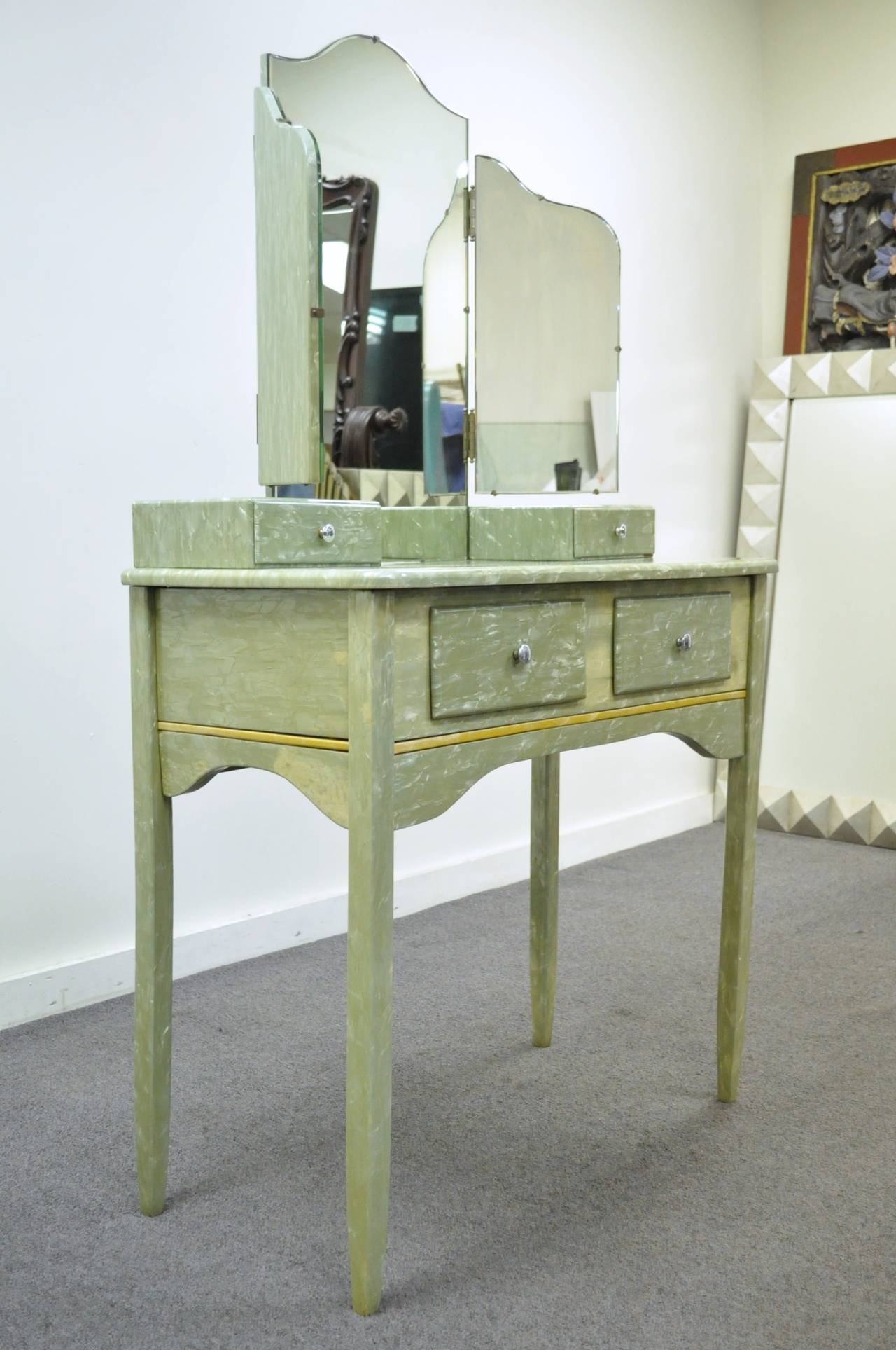 Extremely unique and interesting vanity with matching tri-fold mirror and vanity bench comprised of real celluloid over wood. This rare set has a very striking appearance, thanks to the iridescent tones of the light green celluloid, and the simple