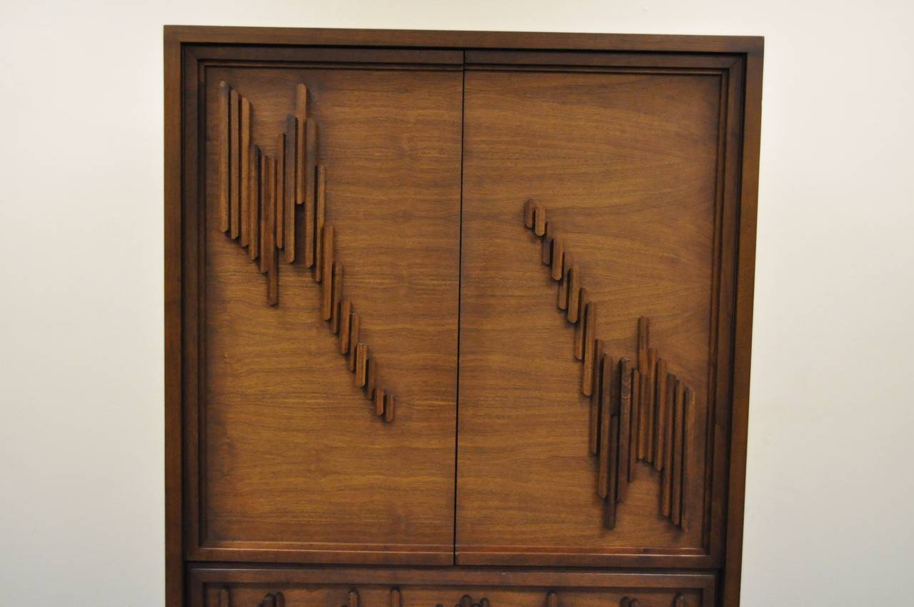 Very impressive mid century brutalist walnut armoire. The armoire has a wonderfully unique sculptural base, interior and exterior drawers and shelving, as well as an abstract geometric sculptural facade. Reminiscent of works by Paul Evans.