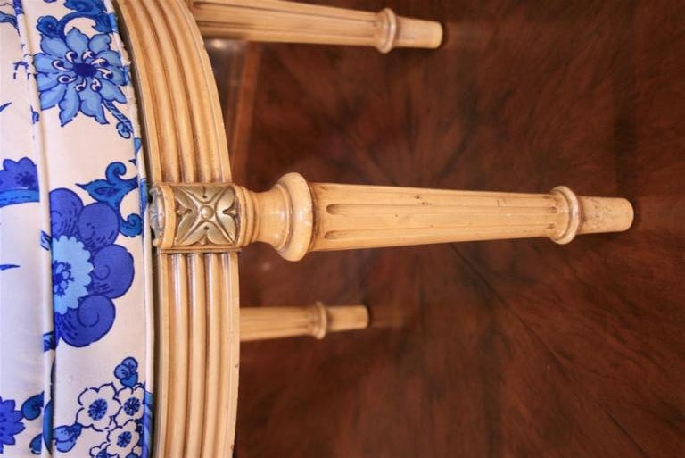 Wonderful French Style Paint Decorated Vanity or Accent Stool with revolving seat. Item features beige paint decoration, carved reeded legs, floral accents, and blue and white whimsical upholstered revolving poof seat.