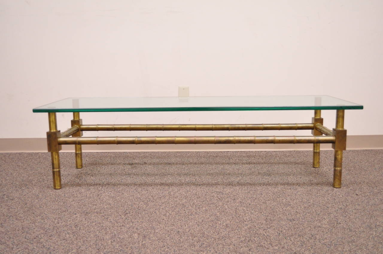 High quality vintage brass and glass, faux bamboo form rectangular coffee table after Mastercraft. This beautiful item features a burnishied/antiqued finish solid brass bass base with a 7/8