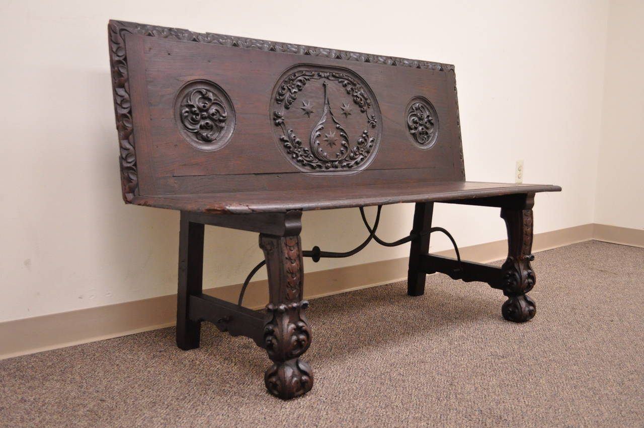 Stunning antique English Renaissance oak bench believed to date back to the 17th century. The piece features a deep relief hand-carved back and legs which terminate at claw like front feet. The base is supported by a hand-wrought iron stretcher in a