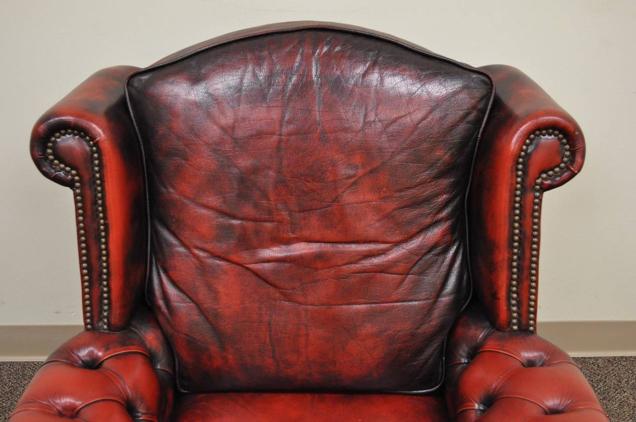 A very impressive and stately vintage, Chesterfield style armchair. The piece features dramatically rolled arms and wings in the English taste, a nicely sloped Silhouette, red antiqued leather upholstery and traditional brass nailhead trim on