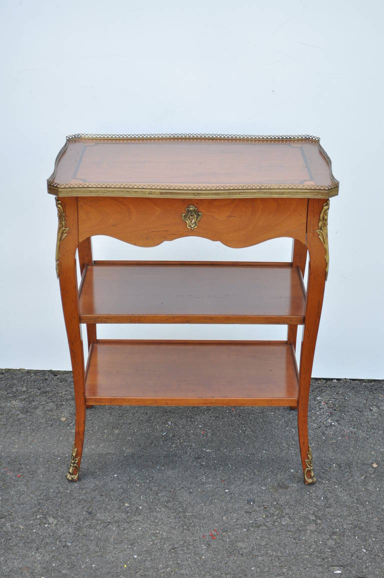 Remarkable Quality French Side Table with single drawer and bronze ormolu in the Louis XV / French Country Taste. The item features superior quality solid cherry wood construction with a single dovetailed drawer, inlaid top, exposed pinned joints,