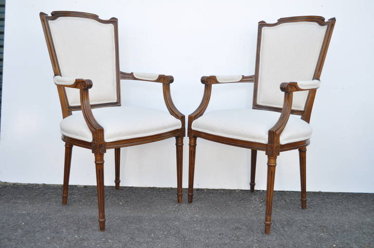 Classy set of six vintage Louis XVI style newly upholstered carved walnut dining room chairs consisting of two armchairs and four side chairs. The set features reeded and tapered legs, shaped backs and new foam, webbing and fabric in an oatmeal