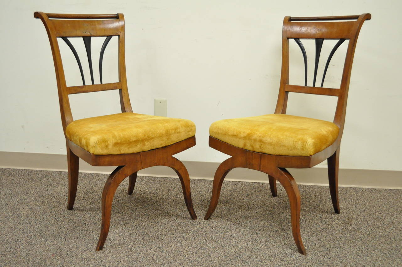 Remarkable pair of Biedermeier Period Side Chairs. The pair features shapely sabre legs, ebonized back splats, rolled backs, beautiful original burl walnut veneer and sold walnut frames, and classic elegant form.