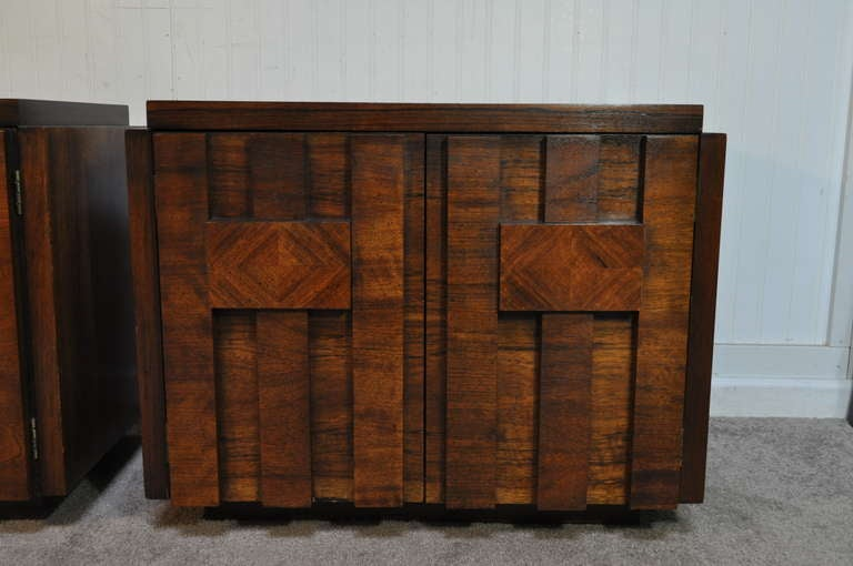 Remarkable pair of Brutalist Mid Century Modern Nightstands by Lane in the Paul Evans Style. The pair features heavy solid wood construction, figured geometric door fronts, and great form. True works of art