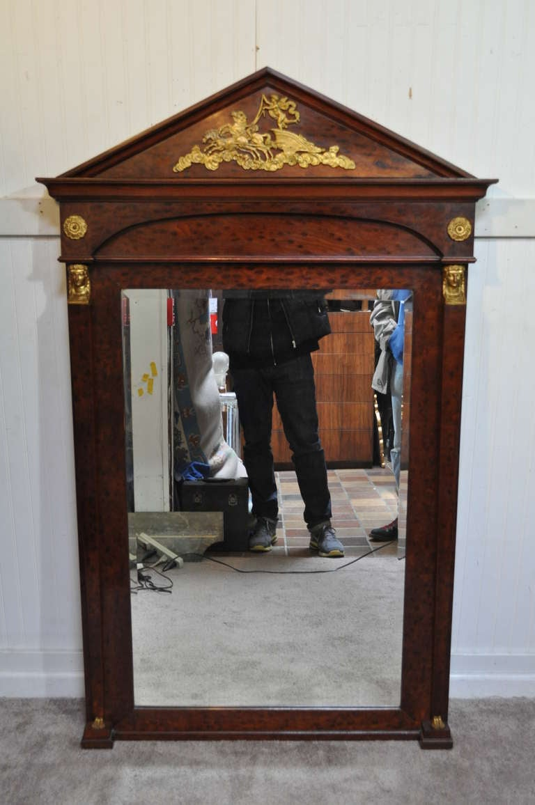 Impressive antique French Empire / Regency style burl wood beveled glass pier mirror with stately bronze mounts including human figured feet, maiden faces, and a cherub upon a horse drawn chariot at the crest.