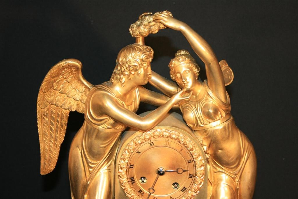 Very fine gilt bronze figural mantel clock featuring cupid (also known as amour) swooning a butterfly winged psyche. This French mantel clock dates back to the early 1800s and is very finely detailed throughout.