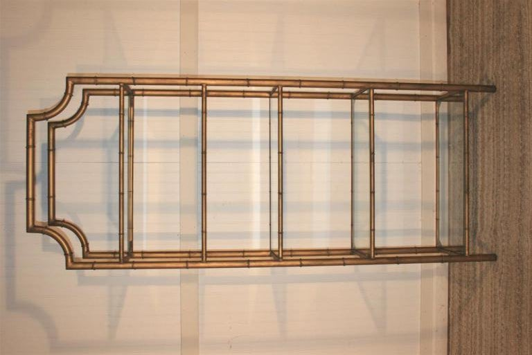 Wonderful Mid Century Modern Antiqued Gold Gilt Metal/Tole etagere. Item features a pagoda top and 5 glass shelves. Can be used as a bookcase or even a display shelf.