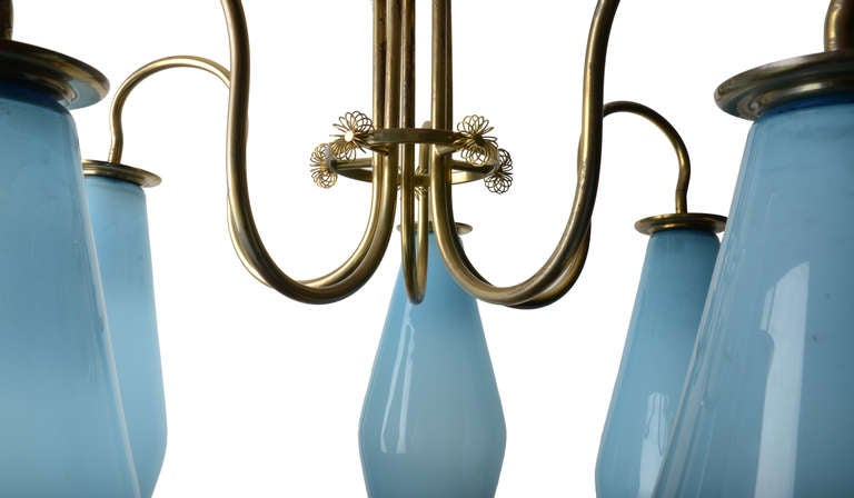 A really stunning Paavo Tynell Chandelier in Brass and Glass.  This example with 5 large blue hand blown glass shades.  The central frame is a delicate flowing armature with a central circle ending in trademark brass blossoms. Incredibly elegant
