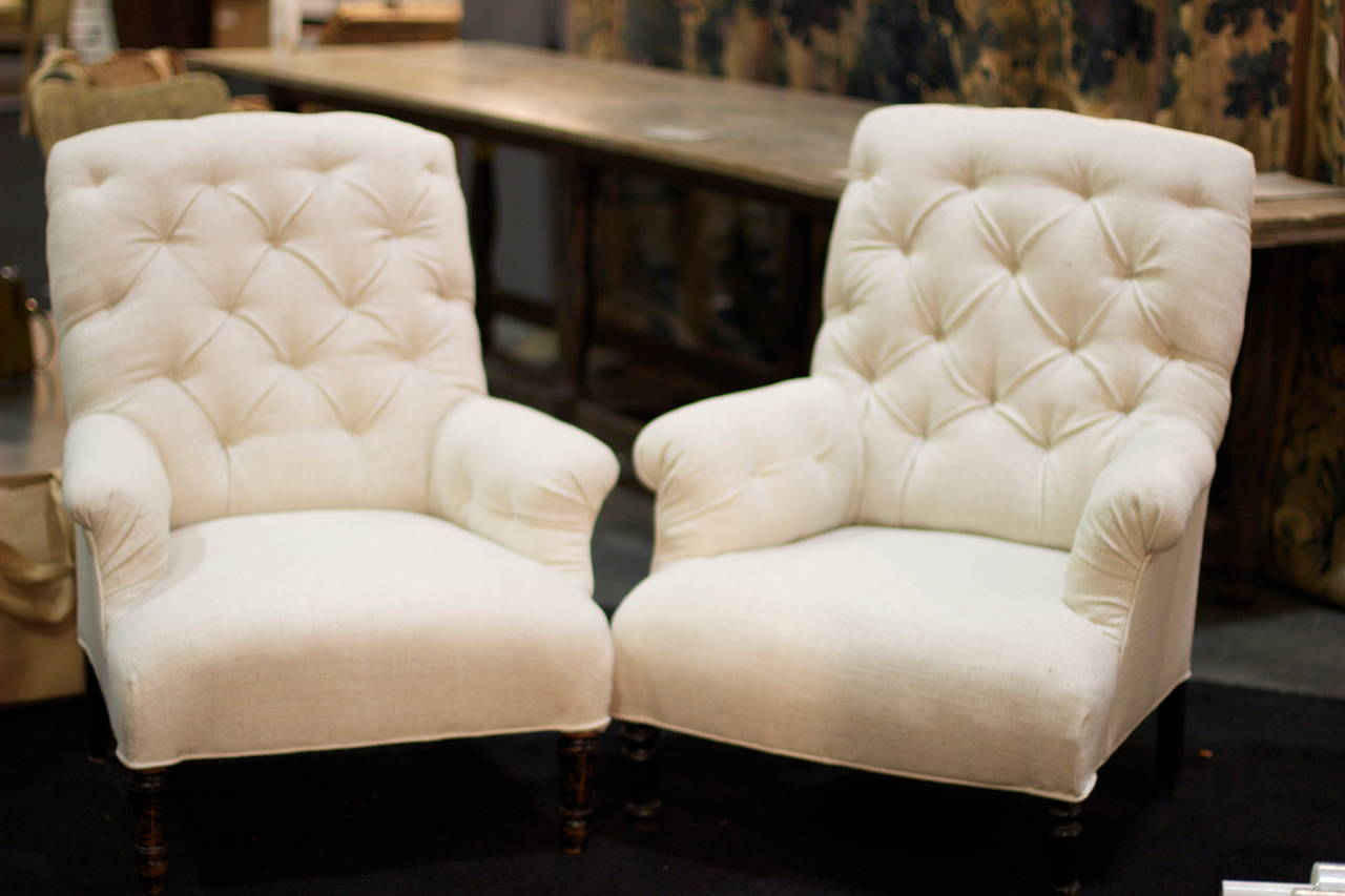 Lovely lines on this pair of French tufted Club Chairs. Newly reupholstered in off white Belgian Linen. Ebonized black turned legs.