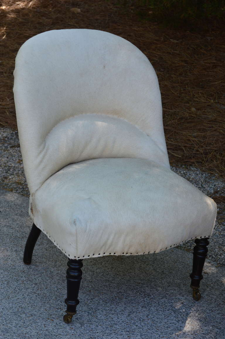 Newly upholstered 19th century French salon chairs with vintage white cowhide leaving the back framework exposed.