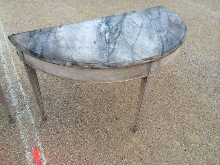 Incredible faux marble painting on this pair of 19th C Swedish demi lune tables. Lovely rosette carving and fluted legs.