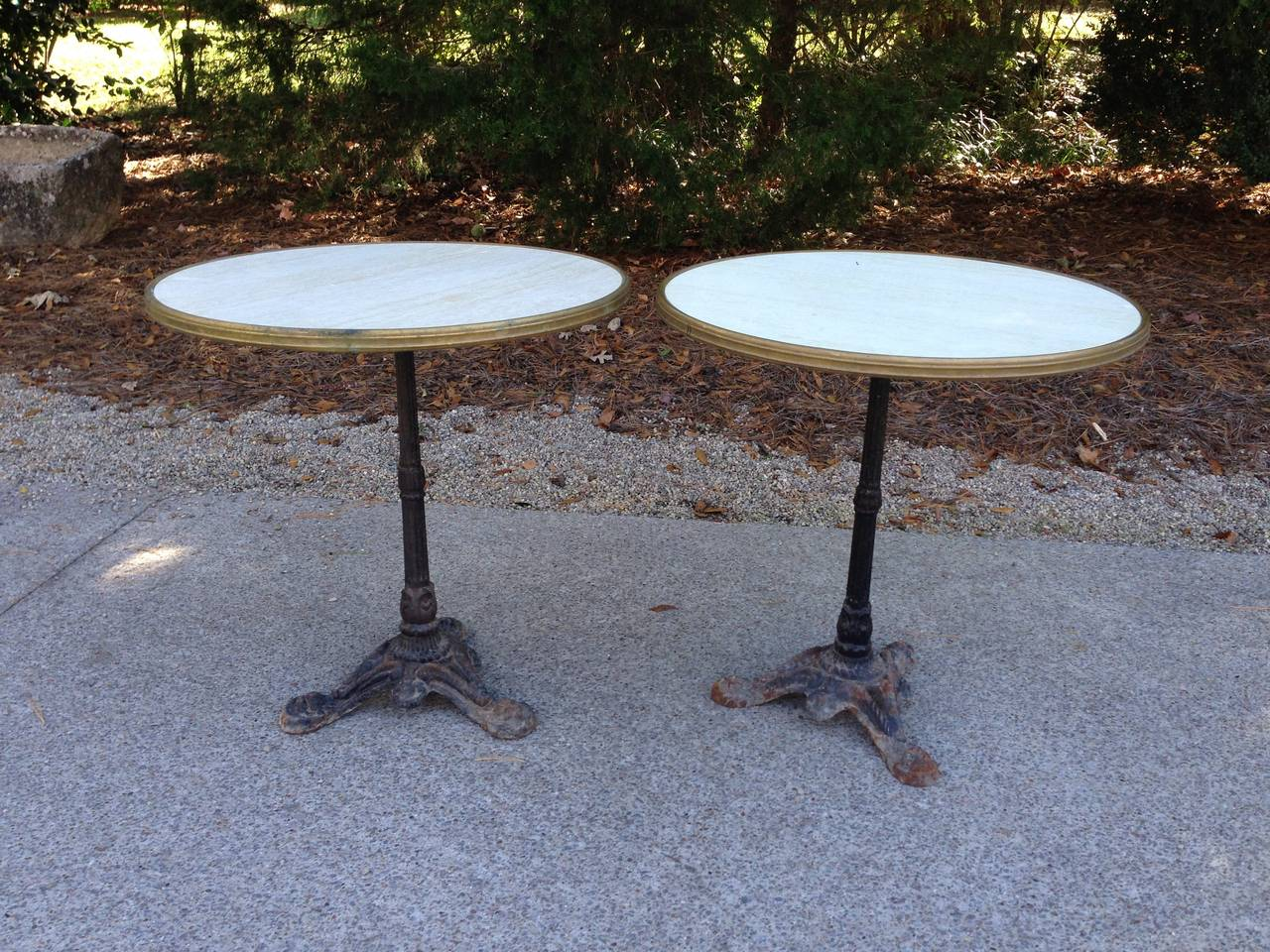 Pair of French bistro tables with faux marble tops,  brass rims and beautiful patinas on the black painted iron bases. Bases date to early 1920's. Priced individually and may be purchased separately.