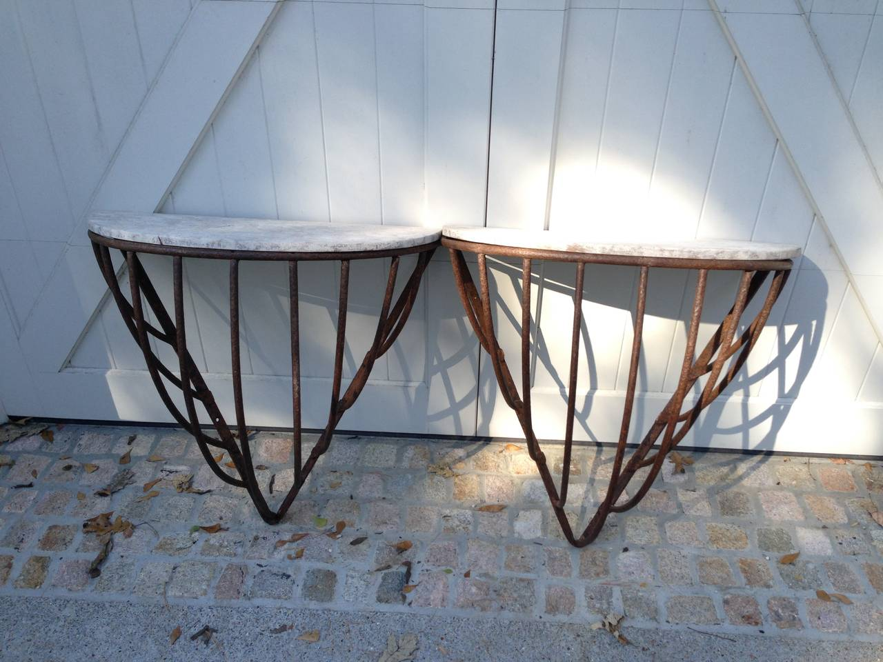 Unusual pair of French Iron Hay Racks made into console tables with Faux Stone painted wooden tops. Tops are old as well. Racks are in perfect condition and can easily be secured to a wall. Priced individually.