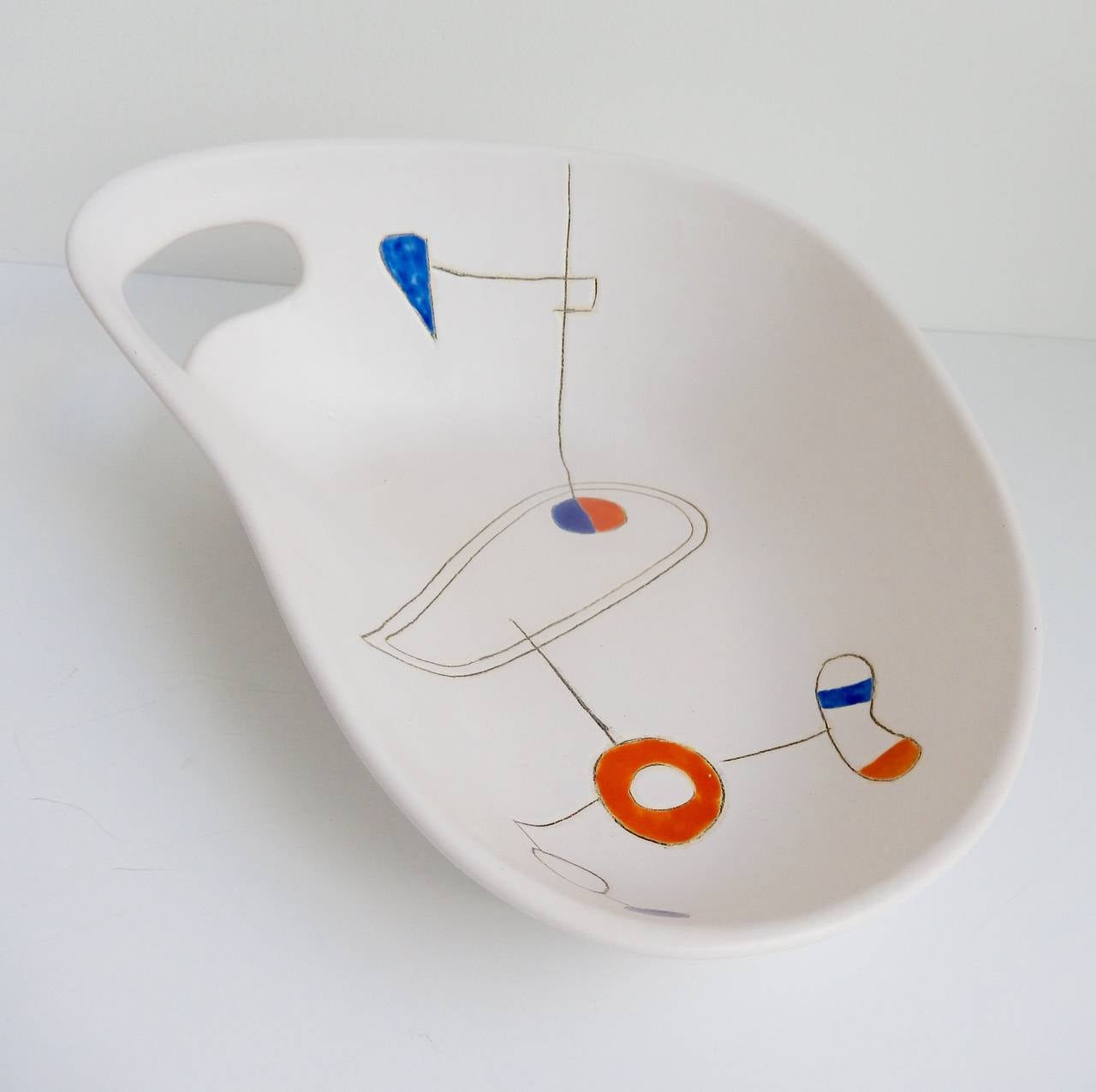 A glazed earthenware bowl with a biomorphic shape and stylized abstract design by the ceramist and painter Peter Orlando (1921-2009). Though born in the US, Orlando studied in France and, along with his wife, Denise, opened a workshop and studio in