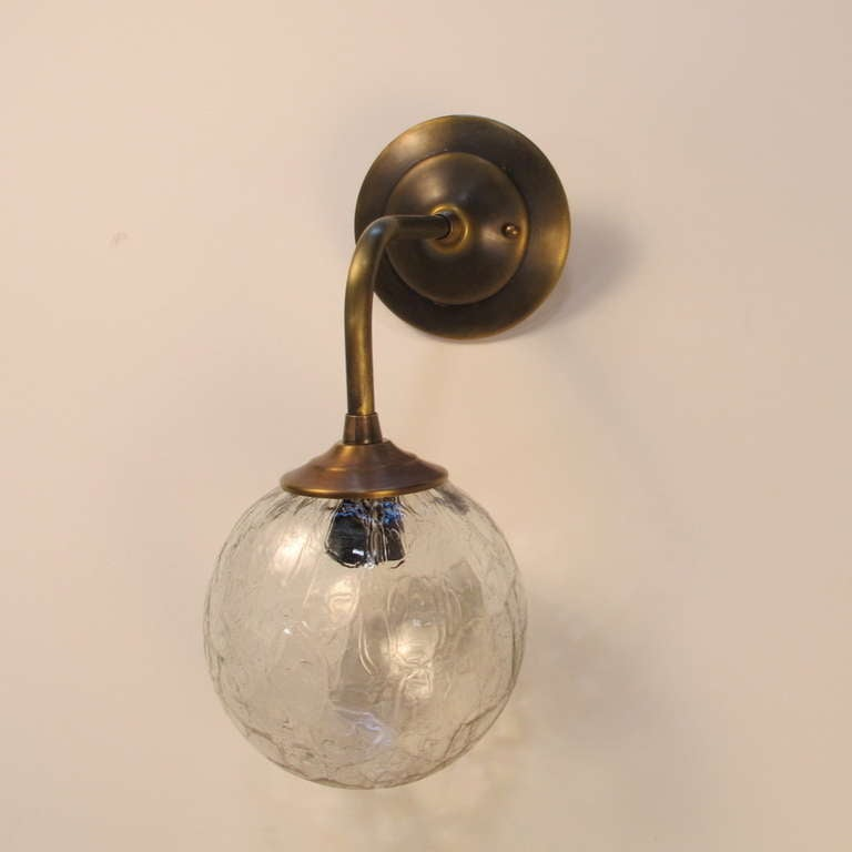 Sconce created with vintage glass globe. The frame is newly made and the glass globe is vintage. These are made to order. Lead time is 4-5 weeks. Single medium base socket up to 60 watts. UL approved. Courtesy to the trade. Finish shown is tarnished