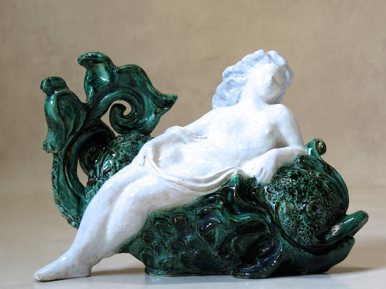 Lovely glazed ceramic representation of a nude woman reclining on a dolphin's back. Craquelure finish on the woman. Signed and dated