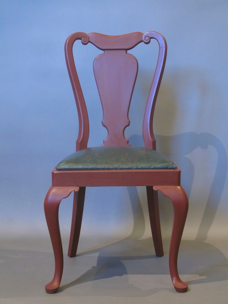 Six Queen Anne style dining chairs, painted red. The seats are upholstered in the original dark green leather. The chairs have vase shaped splats and are raised on elegant cabriole front legs ending in pad feet.