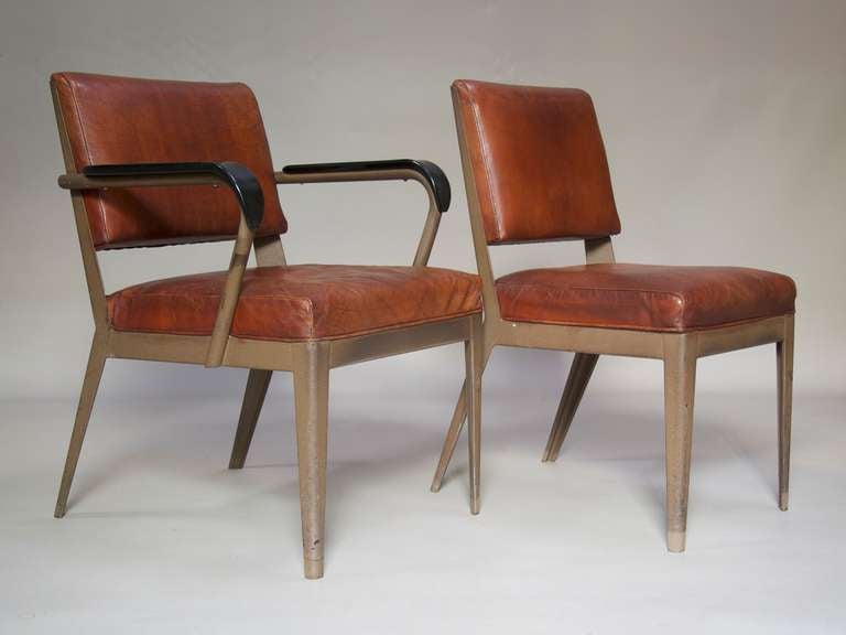 Matching chair and armchair with a painted  iron structure, upholstered in rich cognac-coloured leather. The armchair has black Bakelite armrests.  Measurements provided below are for the armchair. The chair measures (in centimeters):  Height: