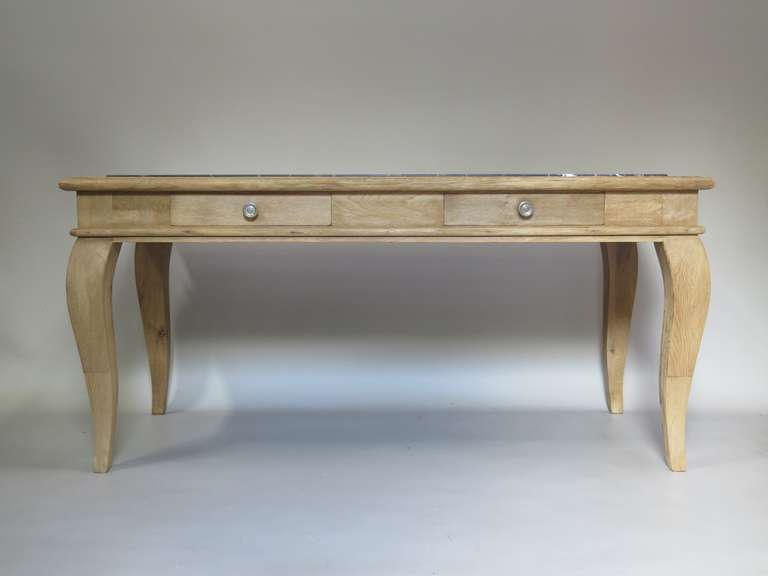 Lovely console or desk of brushed oak, with a slightly raised marble top framed by an oak surround. Elegant lines. Raised on generous cabriole legs. One side of the apron has a mustache shape; the other contains two drawers. The marble is matte
