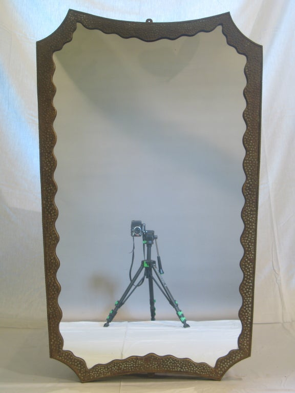 Made of wrought and hammered iron, subtly gilded, with touches of verdigris.  Demilune reddish marble top.  Dimensions below are for the console table. The dimensions of the mirror are as follows (in centimeters): Height 128 Width 79