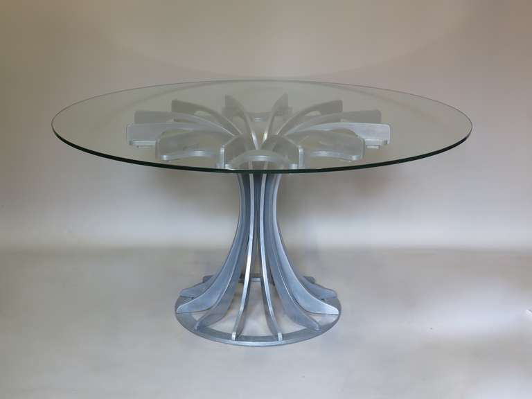 Wonderful circular dining or centre table with a heavy cast aluminium base and a thick glass top.