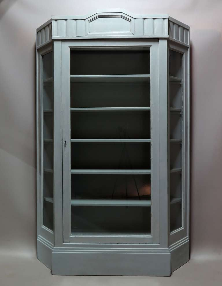 Elegant bookcase or vitrine or display case with canted corners, glass front and sides and an Art Deco cornice. Painted a very delicate light green or grey color.