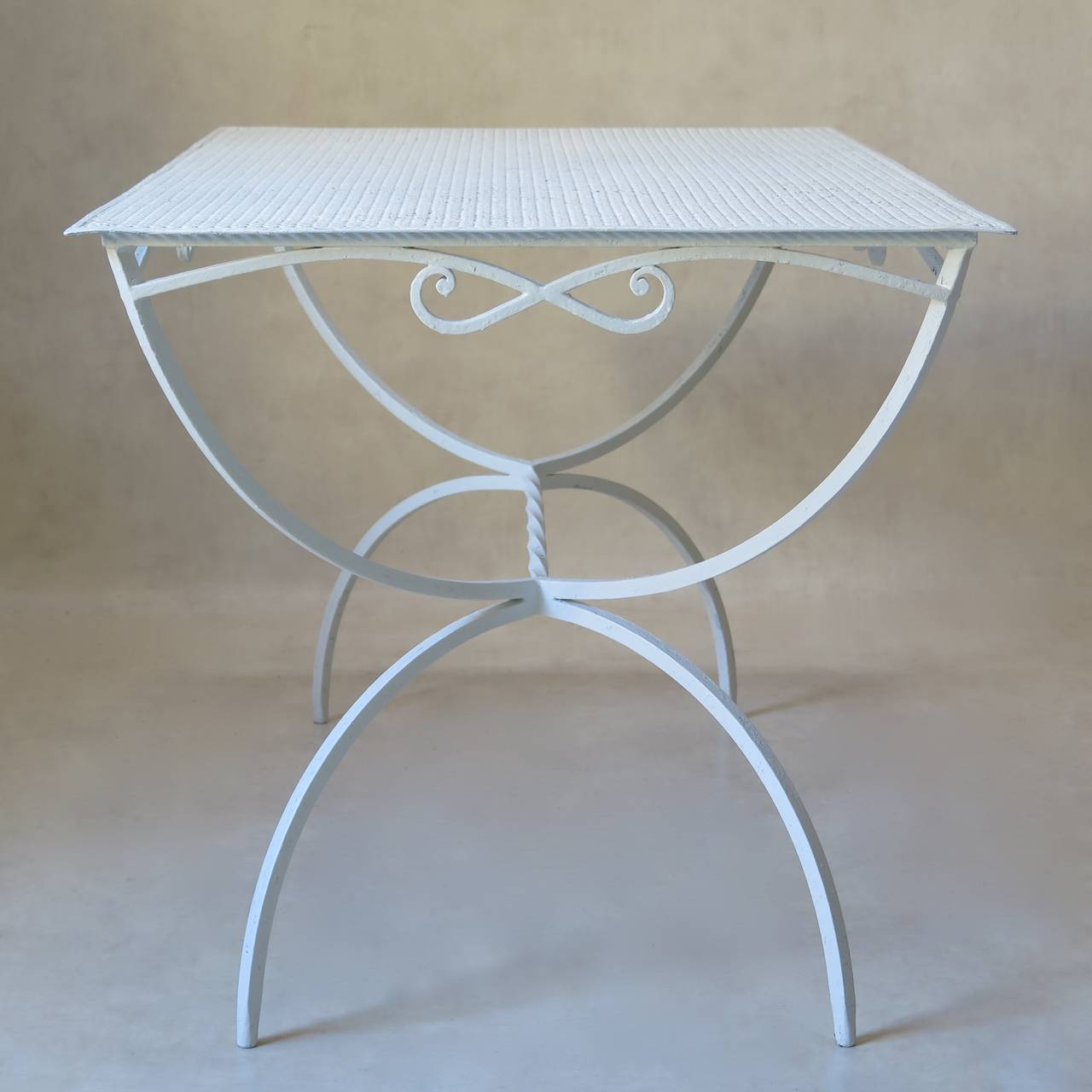 Rectangular wrought iron garden dining table by Maison Jansen. The tabletop is made of cloverleaf patterned sheet metal. The apron is decorated with a bow on all four sides. Curule style base, joined by a twisted iron stretcher.  Also available