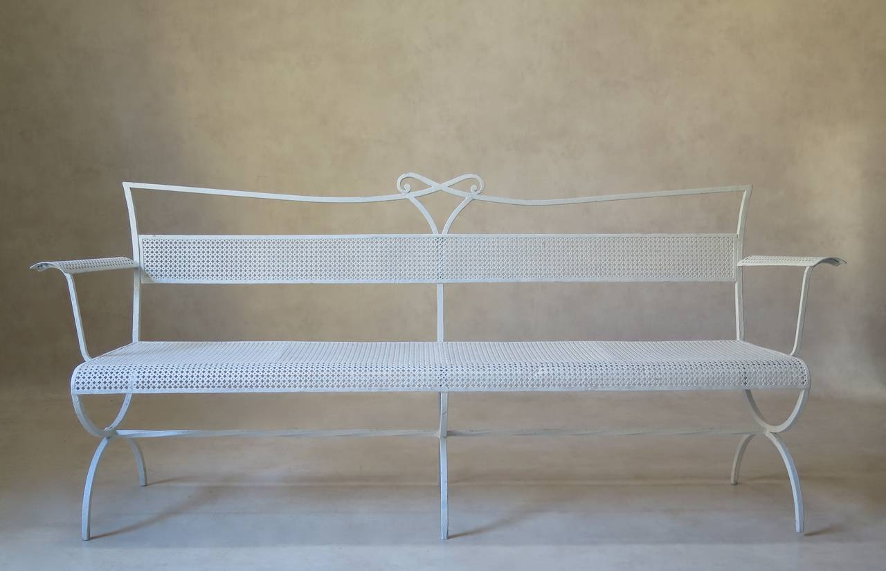 Elegant and chic long bench by Maison Jansen. Bow motif in centre of crest rail; curved armrests and seat edge. Raised on a Curule-shaped base, reinforced by a twisted iron stretcher. The back, seat and armrests are made out of cloverleaf patterned