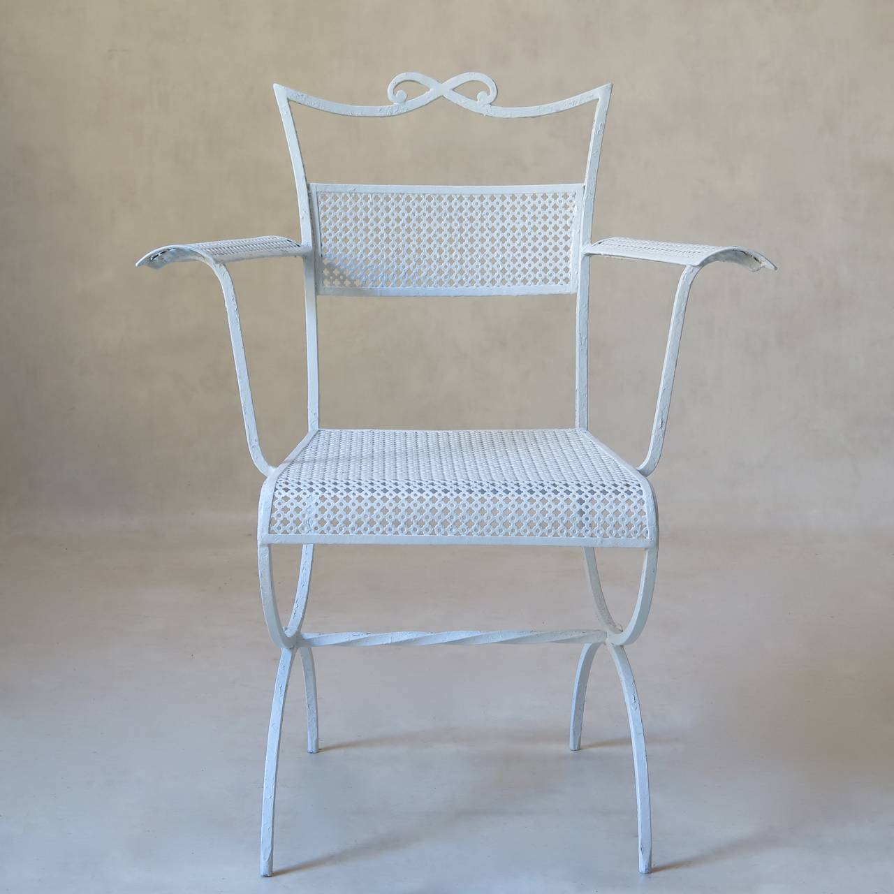 Charming pair of bow-motif wrought iron armchairs by Maison Jansen. Elegantly tapering backs, with a bow on crest rail. Curved armrests and seta edge. Curule-shape bases, joined by a twisted iron stretcher. The seats, backs and armrests are made out