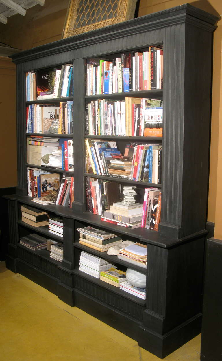 Large bookcase in two parts (top and bottom), with shelving. Painted black.