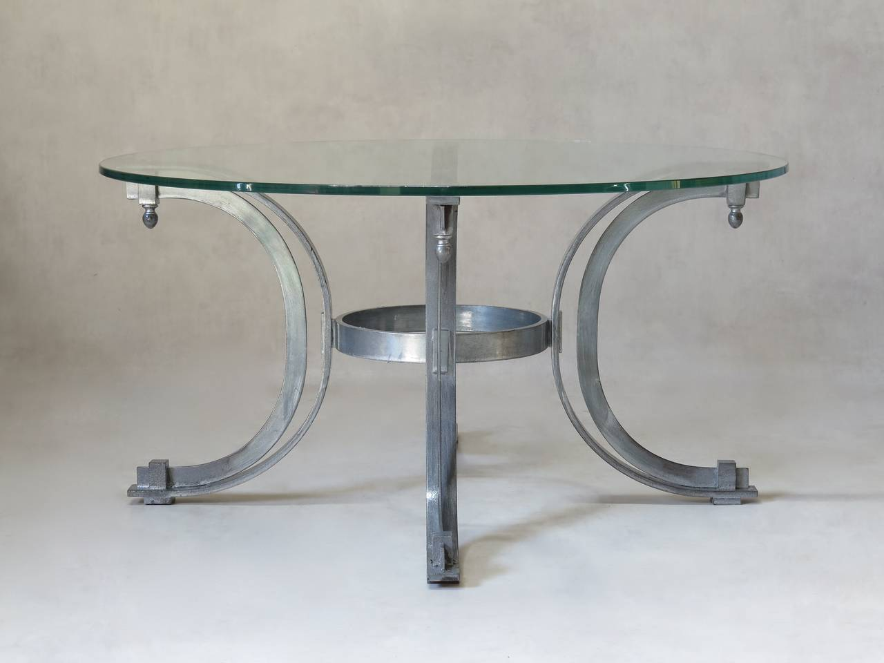 Chic neoclassical style round coffee table. The thick clear glass top is supported by four C-form legs ending in finials and joined by a circular stretcher.  We have four tables available. They are identical except for the finials, which vary from