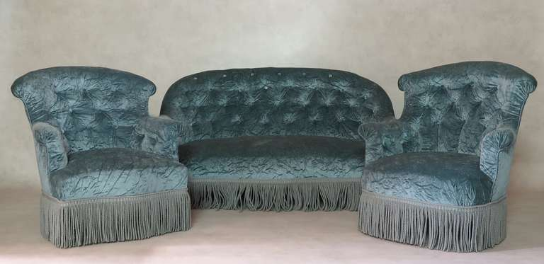 Napoleon III two-seater settee and two armchairs, with button-tufted backs, upholstered in a lustrous silvery-blue crushed velvet, with bullion fringe. The set has a rolled edge.   There is a slight difference between the two armchairs: one has a