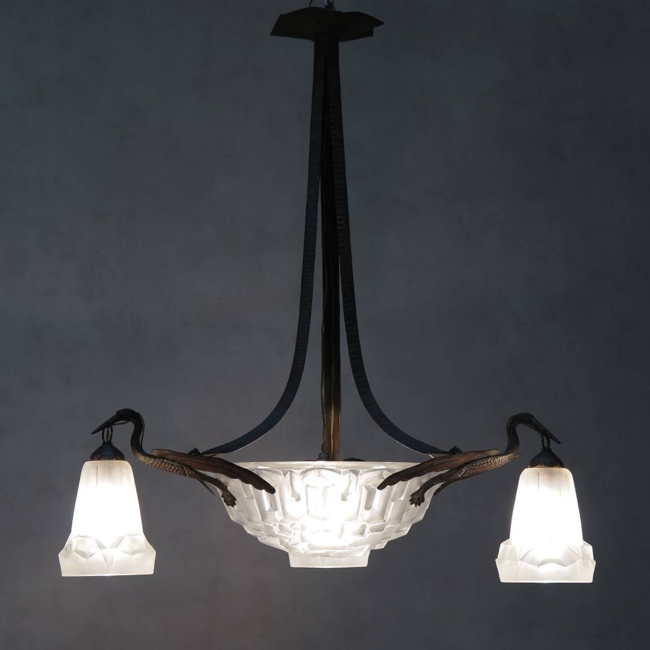 Elegant Art Deco chandelier with a hammered wrought-iron structure and heavy frosted glass shades. Three storks support the large centre shade, and each carries a smaller one in its beak. 