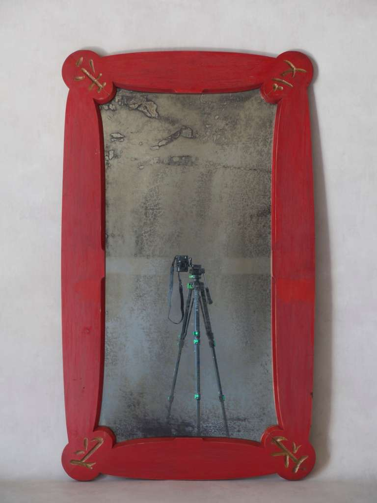 Large Chinese Art Deco style mirror with a wooden frame painted red and engravings picked out in gold at each corner.  Distressed mirror.