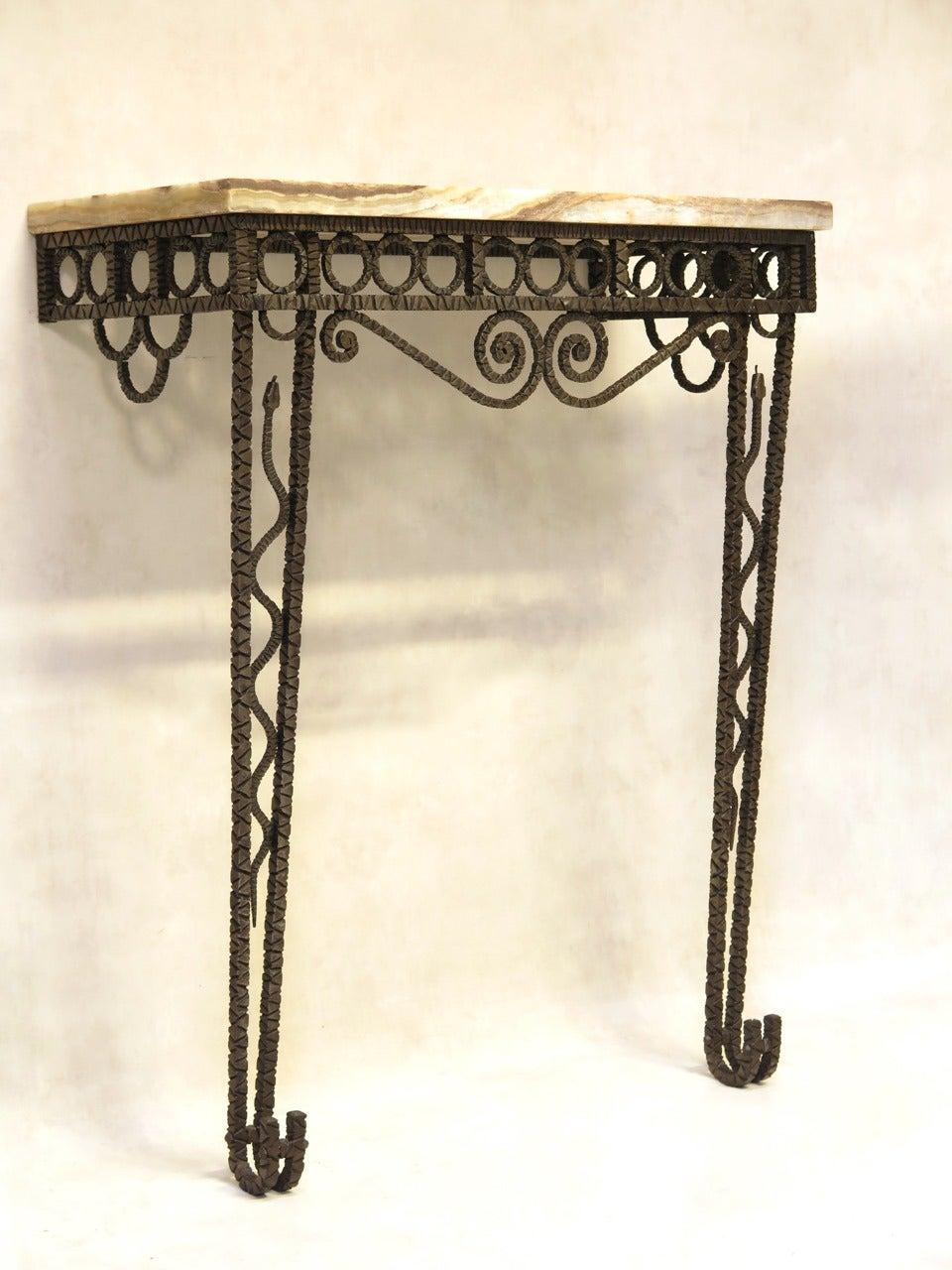 Striking Art Deco console in hammered wrought-iron with a decorated with a snake on each leg. The tapering legs end in elegant outwardly upturned feet. The apron is decorated with a frieze of circles, and scrolling arabesques. The top is made of a
