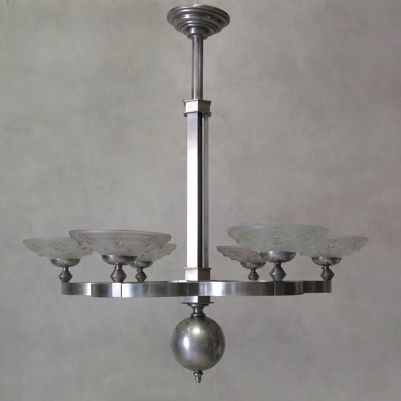 Chic and unusual large, six-light Art Deco chandelier in chromed metal with frosted glass shades, ending in a large finial. Beautiful quality.