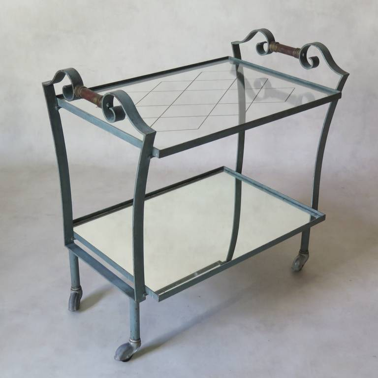A charming late Art Deco drinks trolley or bar cart, with original blue and green patina and handles painted dark red. Two tiers: the lower shelf is fitted with a mirror; the top one with glass etched on the reverse with a gilt diamond pattern. The
