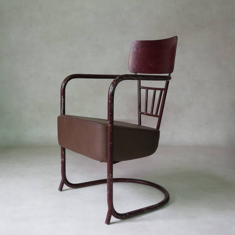 Unusual tubular iron armchair with a cantilevered base and a very large vinyl-upholstered seat. The metal is painted in shiny reddish-brown.