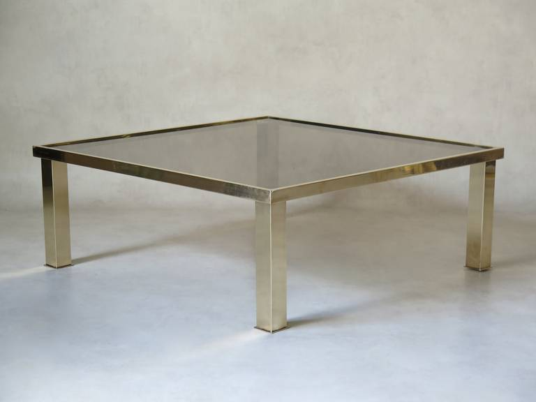 Chic and minimalist square coffee table. The bass is brass and the top smoked glass.