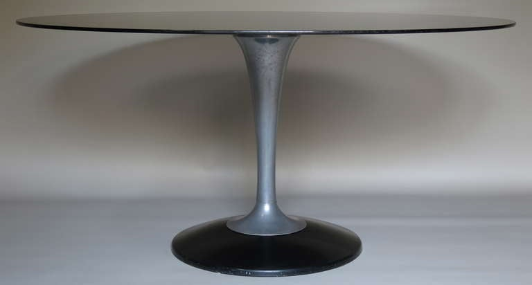 Oval dining/center table with a smoked glass top and tulip-shaped base of cast aluminum and black moulded plastic.