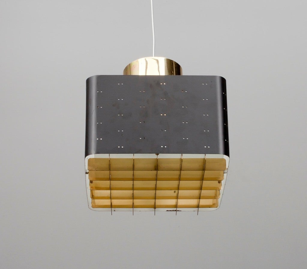 A Chandelier by Paavo Tynell for Idman Oy. Finland. Black and white painted sheet metal, perforated screens, brass grille and sandblasted glass. With manufacturer's stamp. Size 24x24 cm.