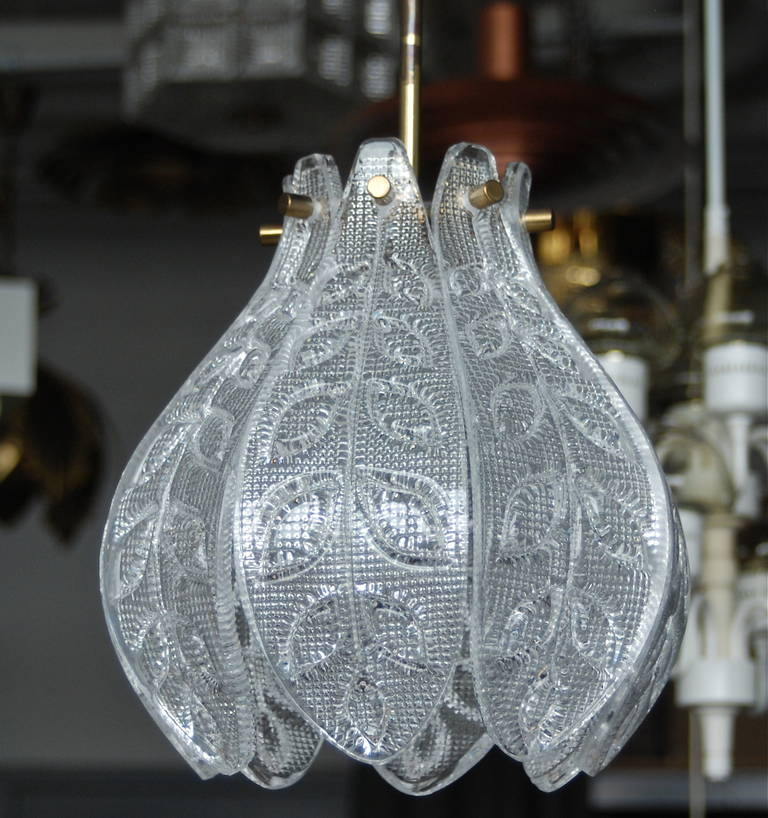 A pendant by Orrefors, Sweden, circa 1960. Textured clear glass with brass hardware. Single, Edison style socket. Existing European wiring, rewiring available upon request.