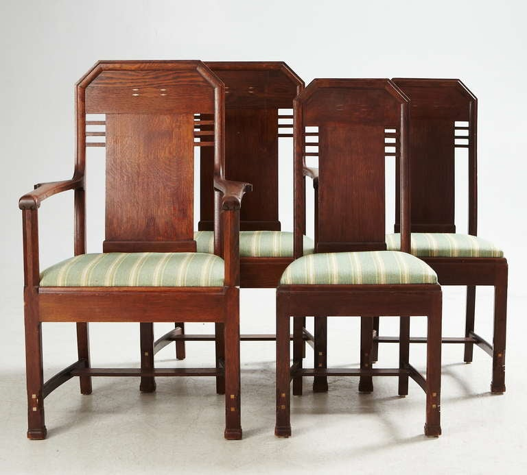 A set of eight jugendstil chairs (two armchairs and six chairs) by Nordiska Kompaniet, Sweden, circa 1912. Design attributed to David Blomberg, chief architect for NK at 1902-1917. Stained oak with pewter inlay decoration on the back and